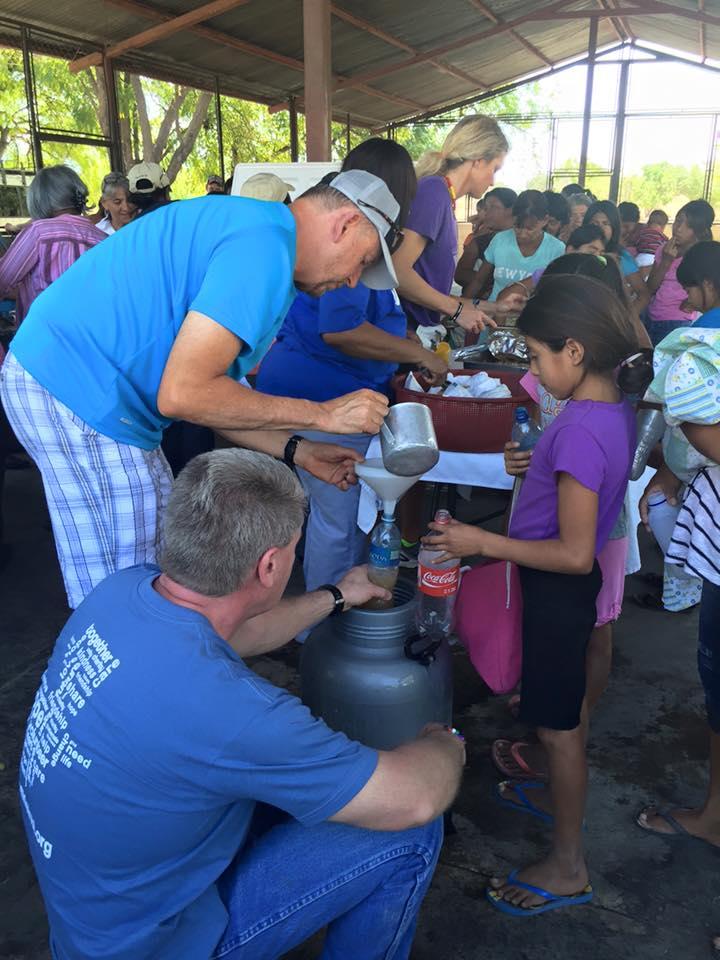 Pastor Steve serving food to villagers