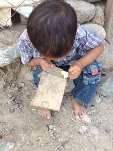 Young boy playing with his only toy... a paper bag