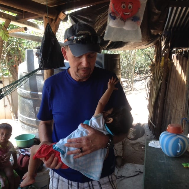 Pastor Steve holding sick infant